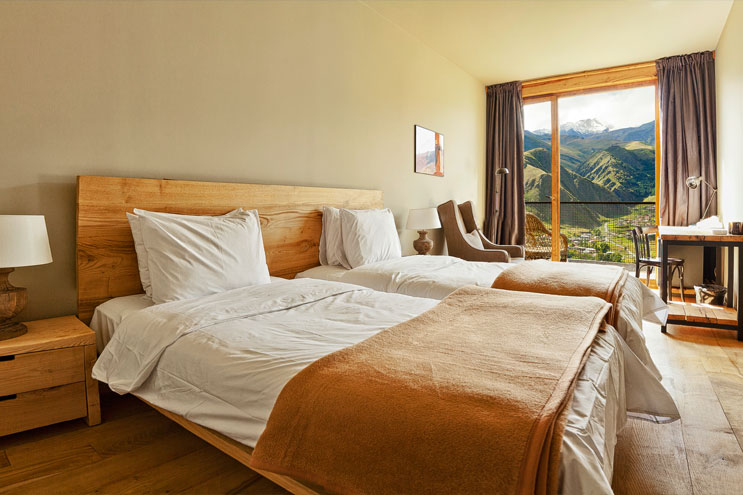 Zimmer mit holz und bergpanorama im rooms kazbegi hotel